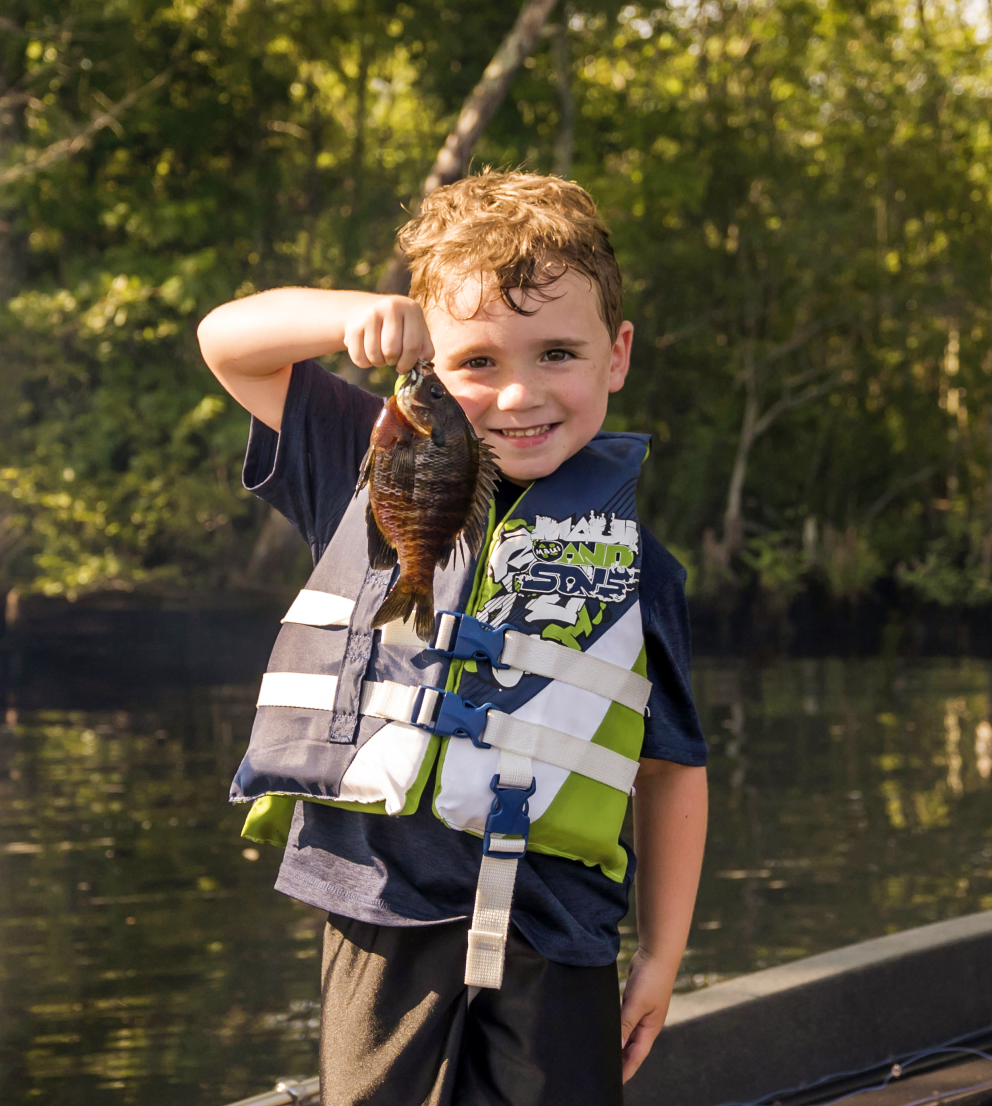 little boy wearing life vest holding up small fish