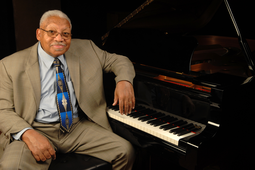 Ellis Marsalis, Jazz Legend, leaning on piano in suit
