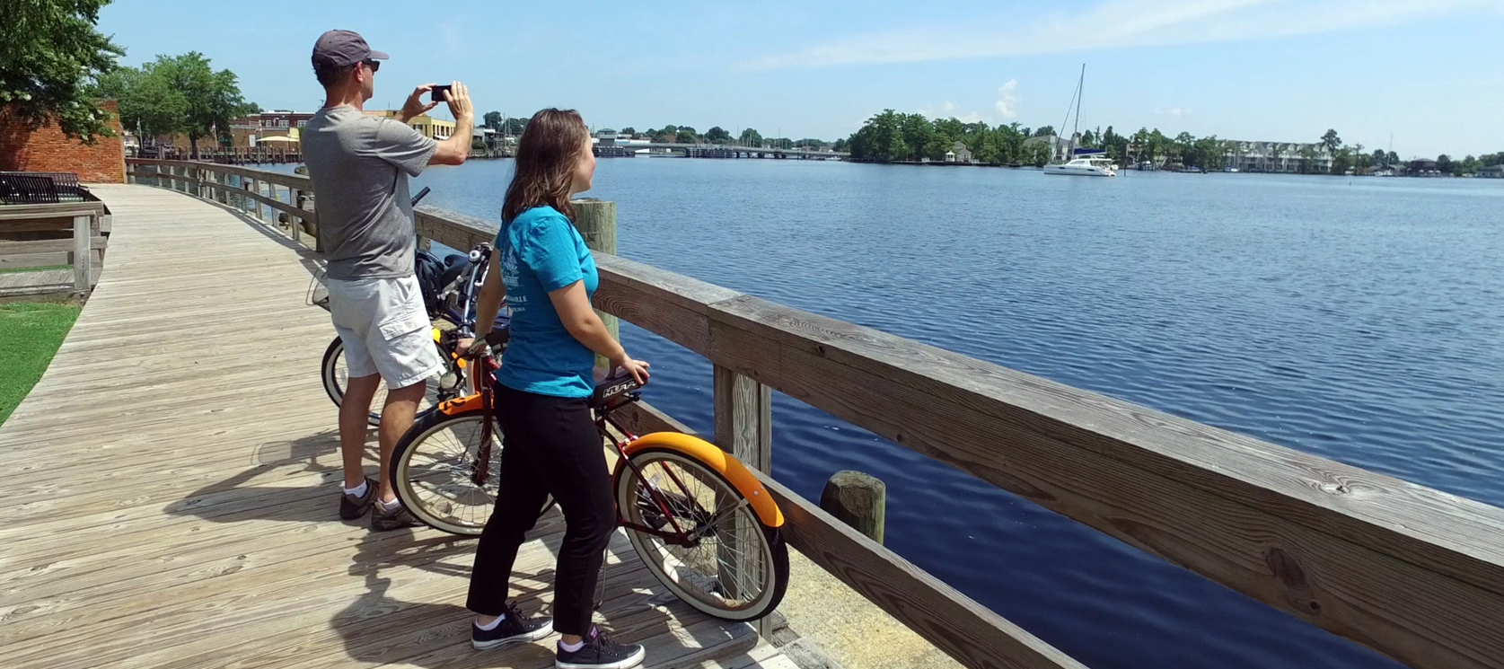 couple with rental bikes at elizabeth city north carolina waterfront taking picture of the river
