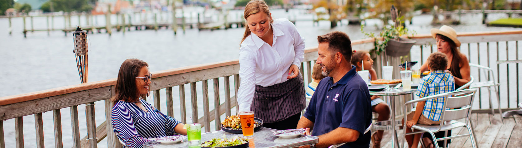 couple being served food on waterfront restaurant patio