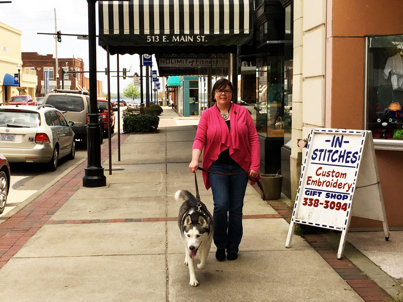 woman walking husky dog on downtown street in elizabeth city, north carolina
