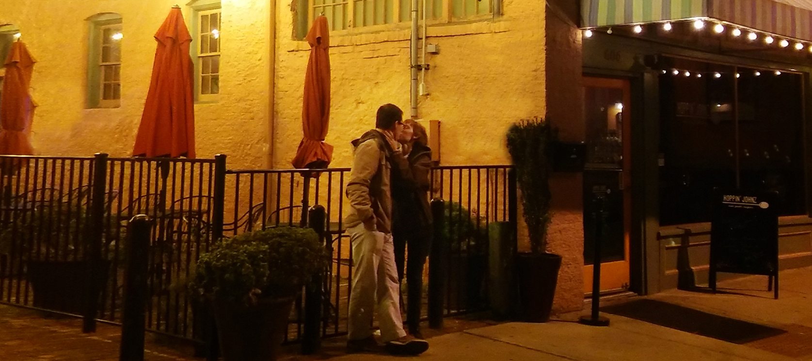 Romantic Couple kissing in front of Pailin's Alley and Hoppin' Johnz