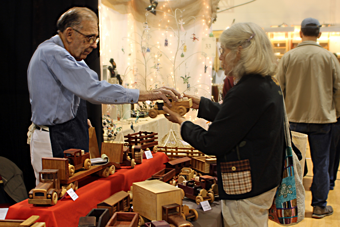 woman buying handmade wooden train from Albemarle Craftsman's Fair