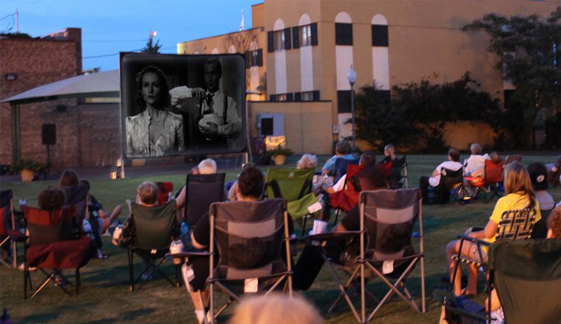 people in lawn chairs watching outdoor movie at Mariners' Wharf Film Festival