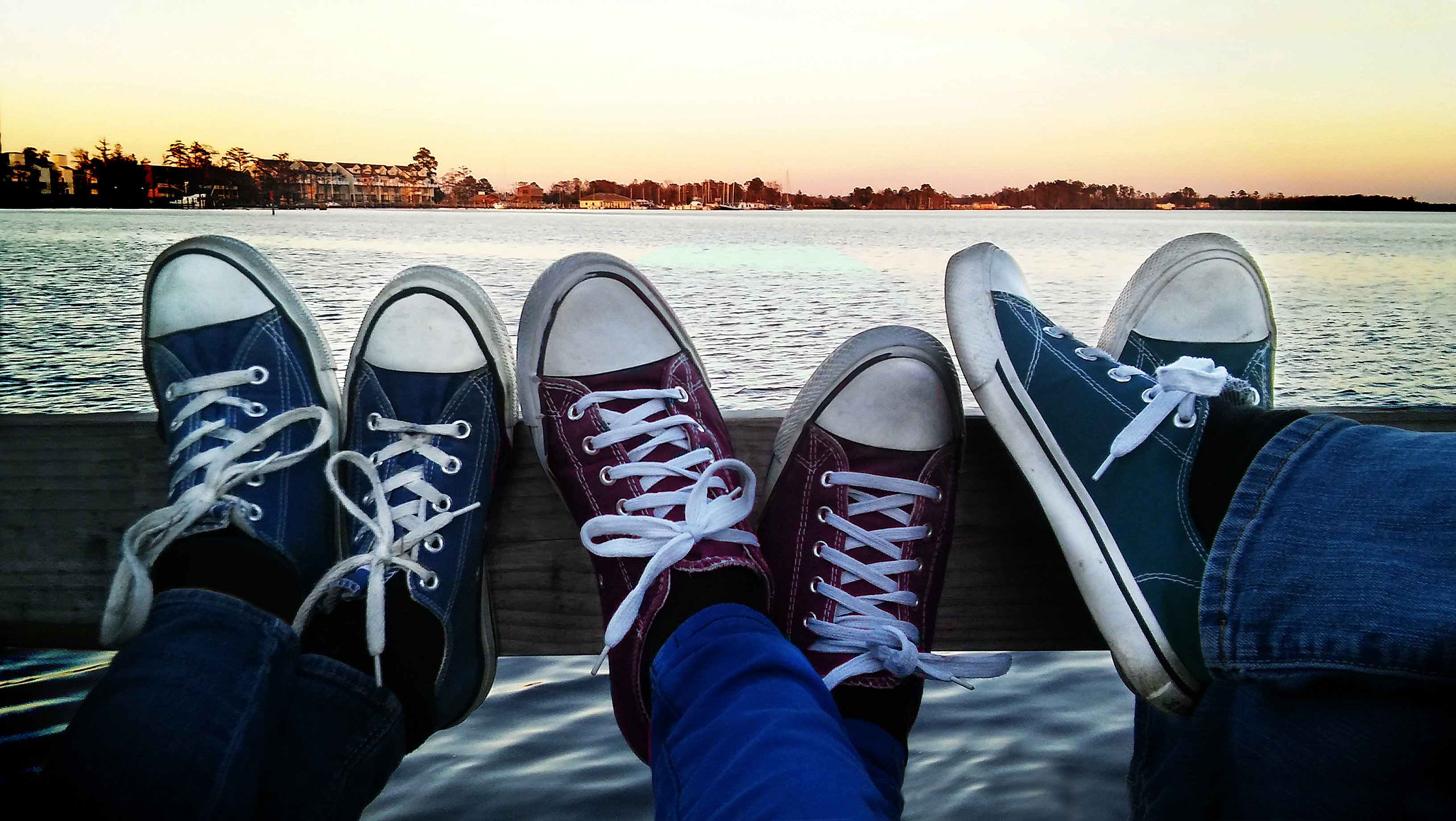 three people wearing converses with feet kicked up overlooking river at Sunset