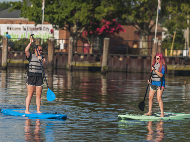 two girls stand up paddleboarding on the waterfront
