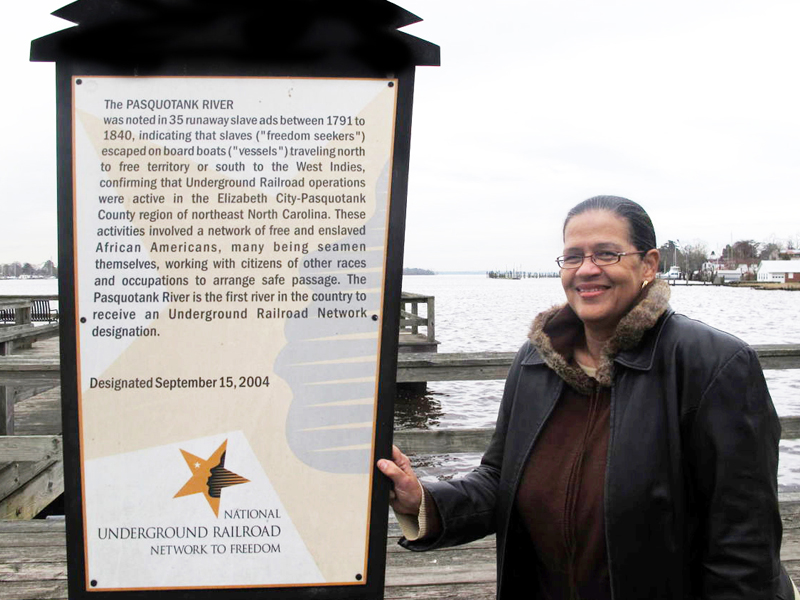 Wanda McLean standing with National Underground Railroad Network to Freedom marker at pasquotank river