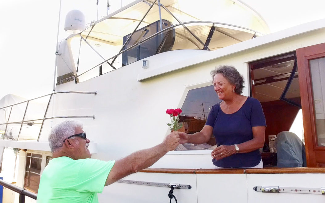 man handing woman rose on boat at dock for Rose Buddies