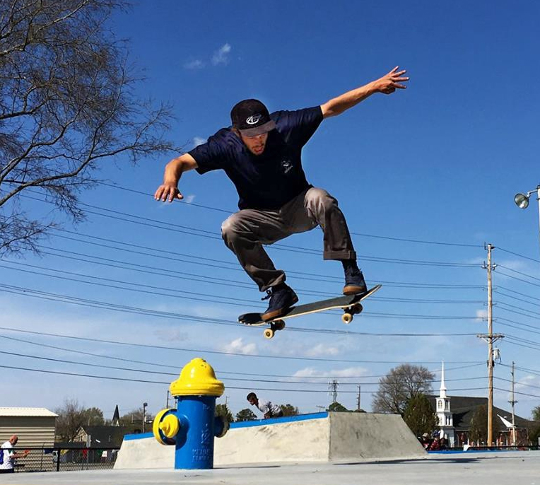 teen skateboarding and doing trick over fire hydrant at Enfield Skateboard Park