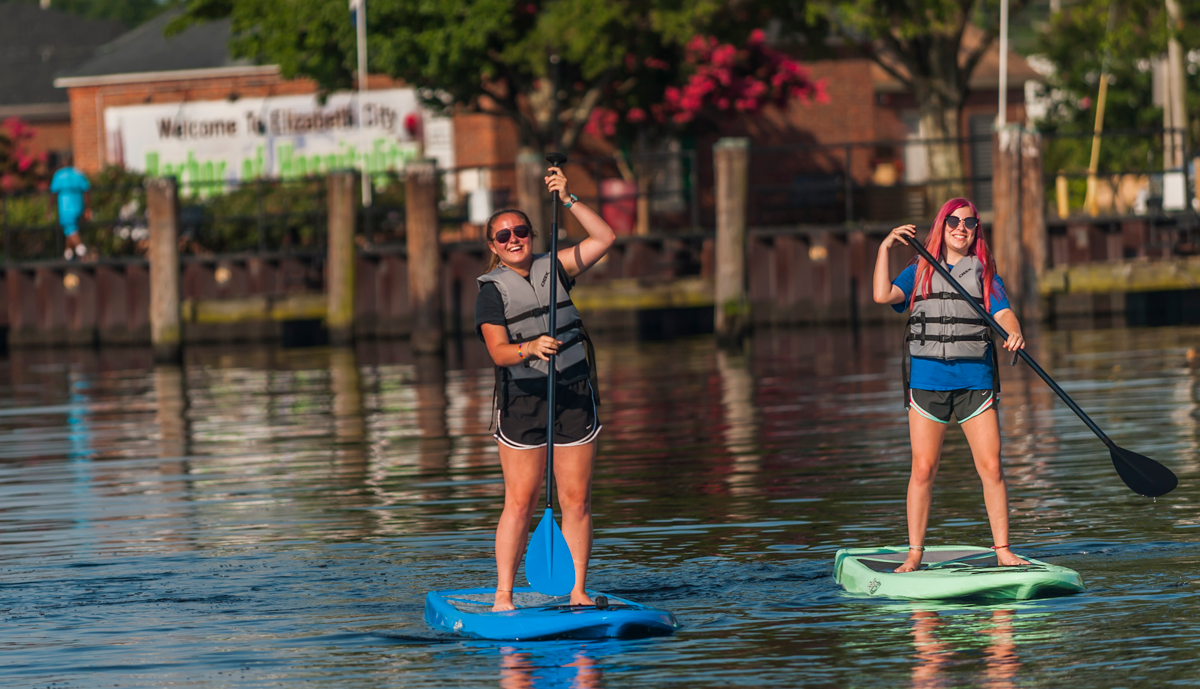 young girls paddleboarding on the waterfront in elizabeth city