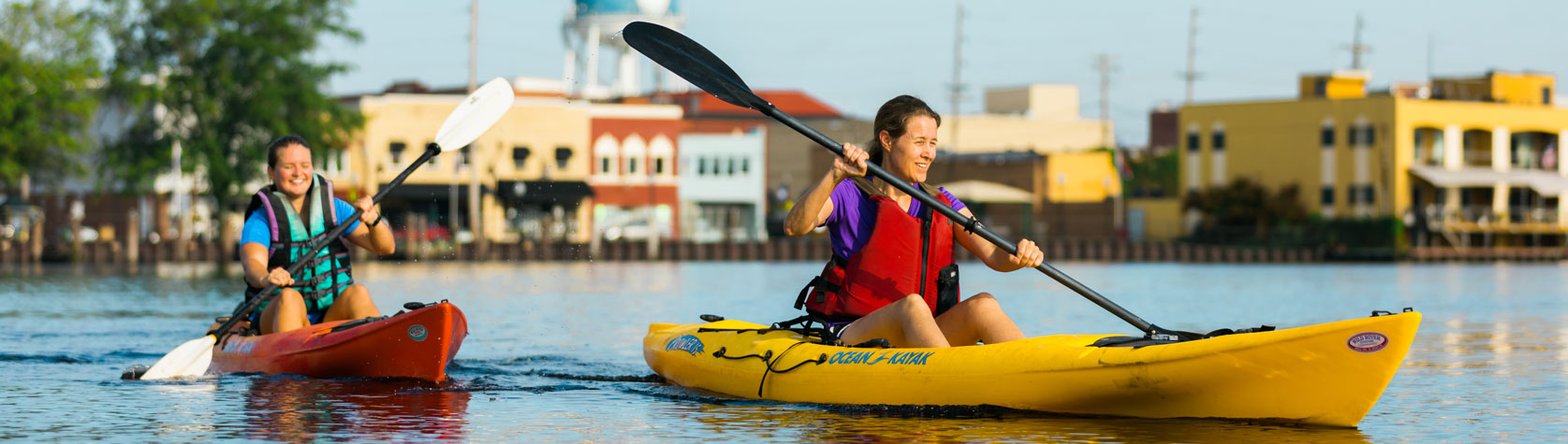 women kayaking on downtown waterfront river with buildings in background