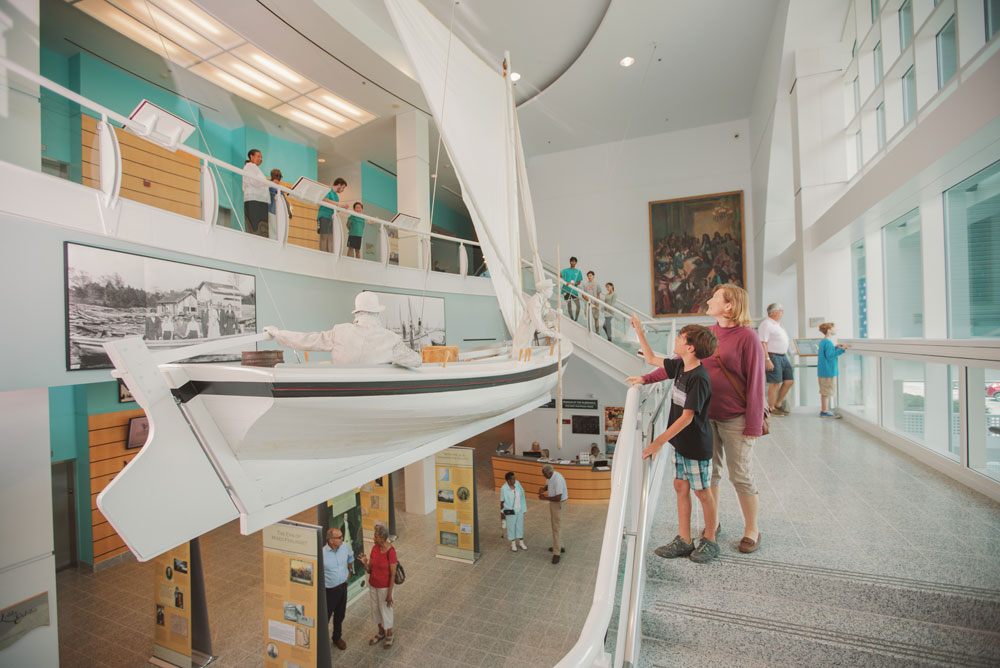 mother and son admiring hanging skiff boat at Museum of the Albemarle