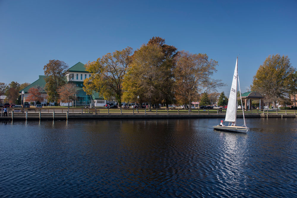sail boat on pasquotank river with museum of the albemarle in the background