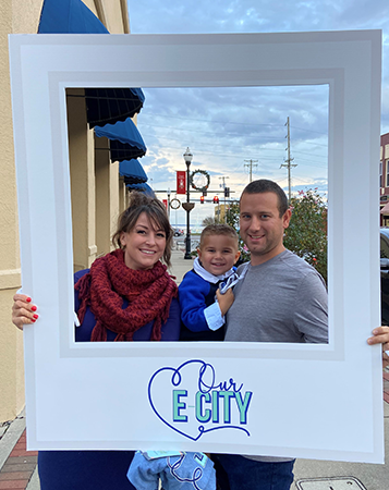 husband, wife, and toddler take selfie with Our E-City sign at ArtWalk in Elizabeth City NC