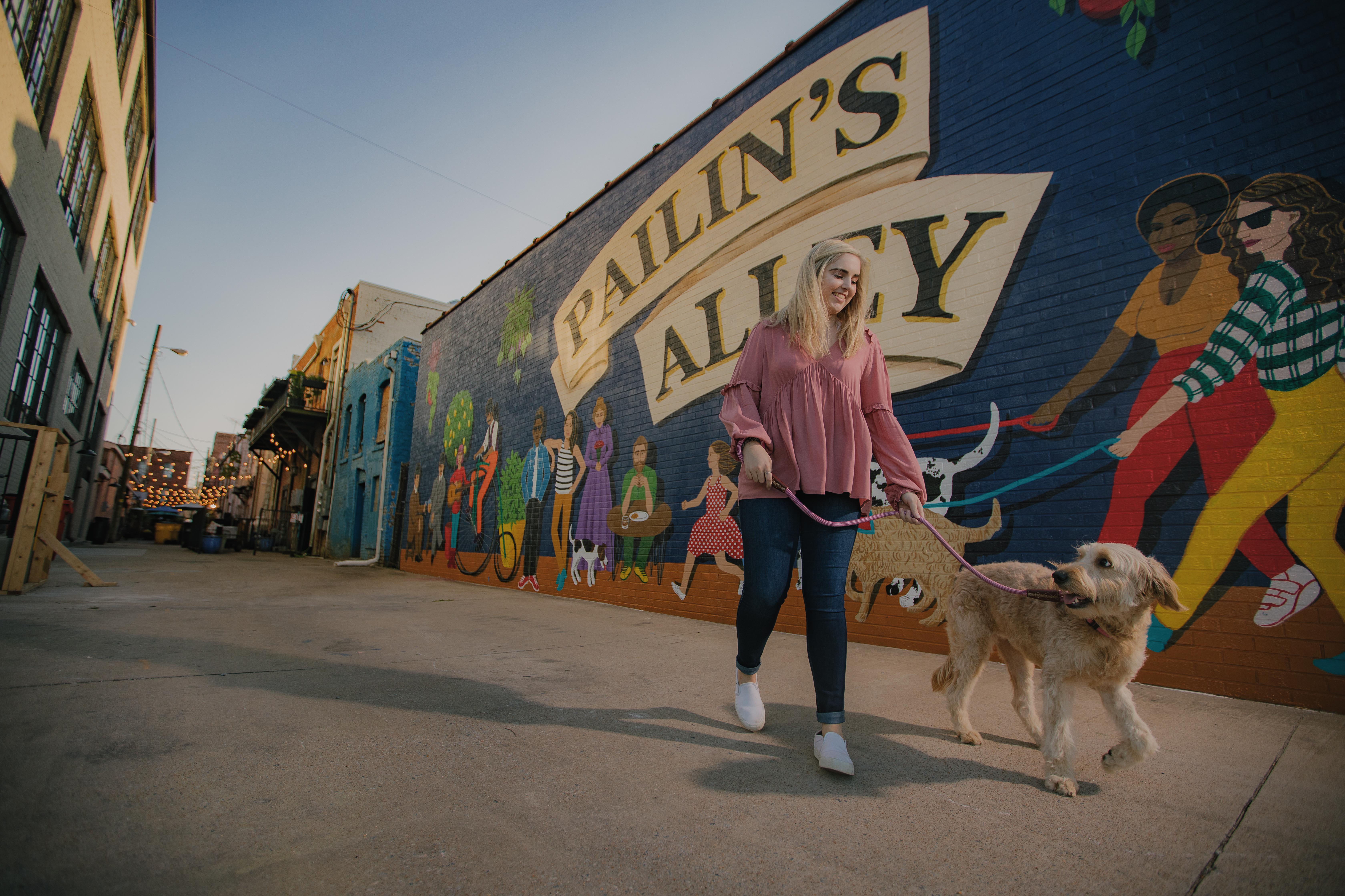 girl walking her golden doodle in front of Pailin's Alley mural
