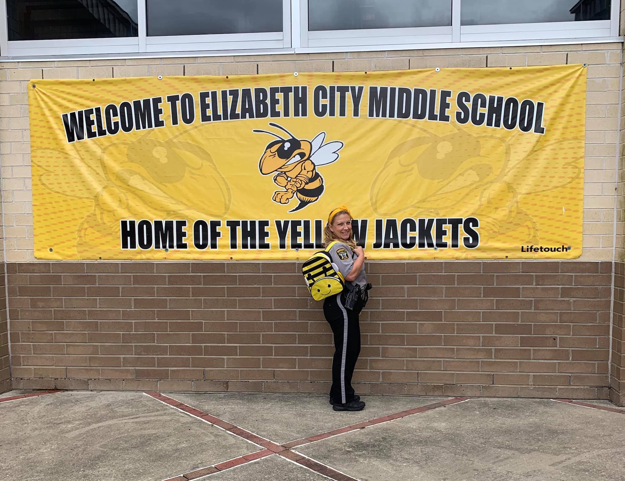Tonie Goldsmith at Elizabeth City Middle School wearing backpack in front of yellow jacket banner