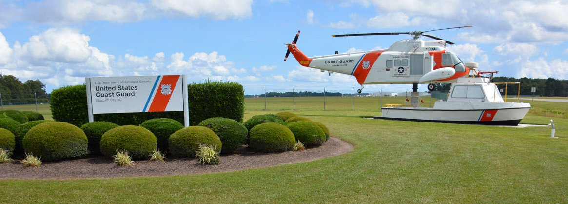 United States Coast Guard decomissioned helicopter and boat at entrance of Base Elizabeth City