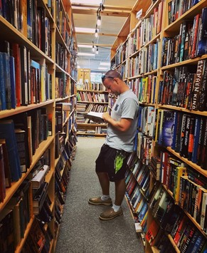 man reading book in bookstore - Elizabeth City, North Carolina