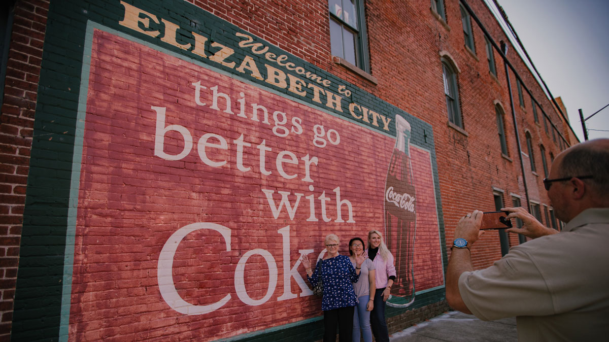 grandma, daughter and granddaughter smiling and posing for picture with coke mural in elizabeth city