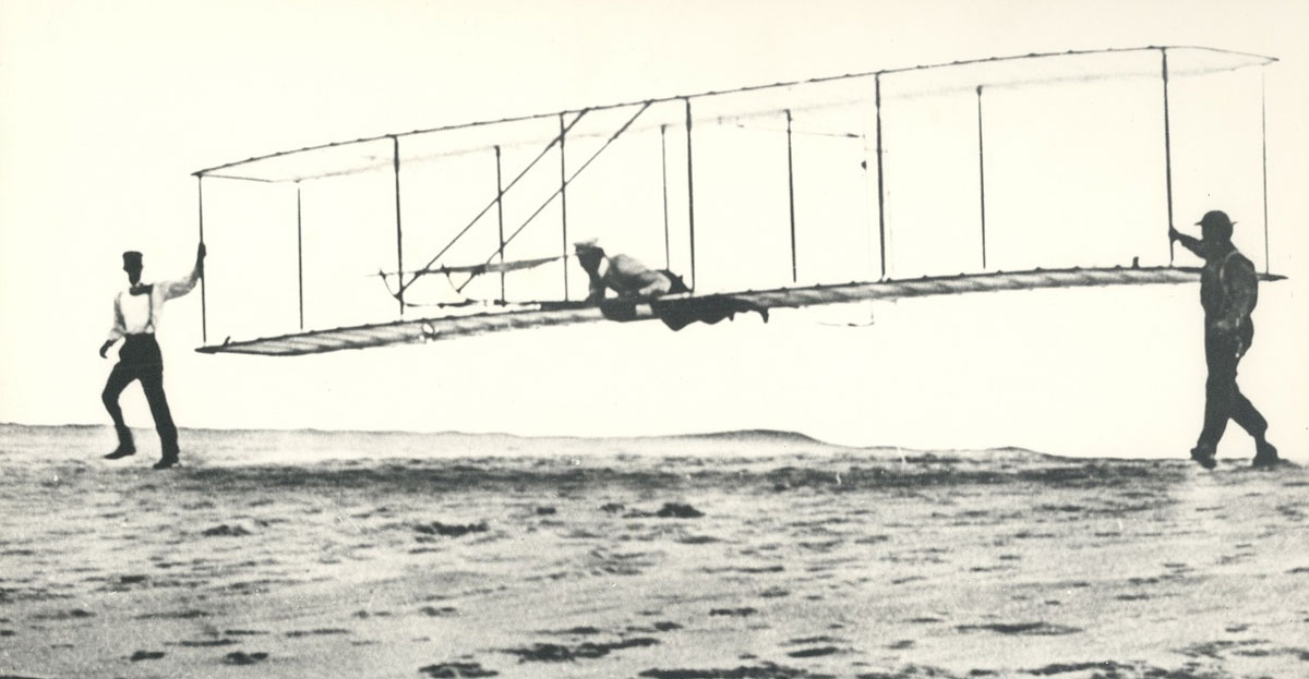 old time photo of the wright brothers taking their first flight in kitty hawk, nc