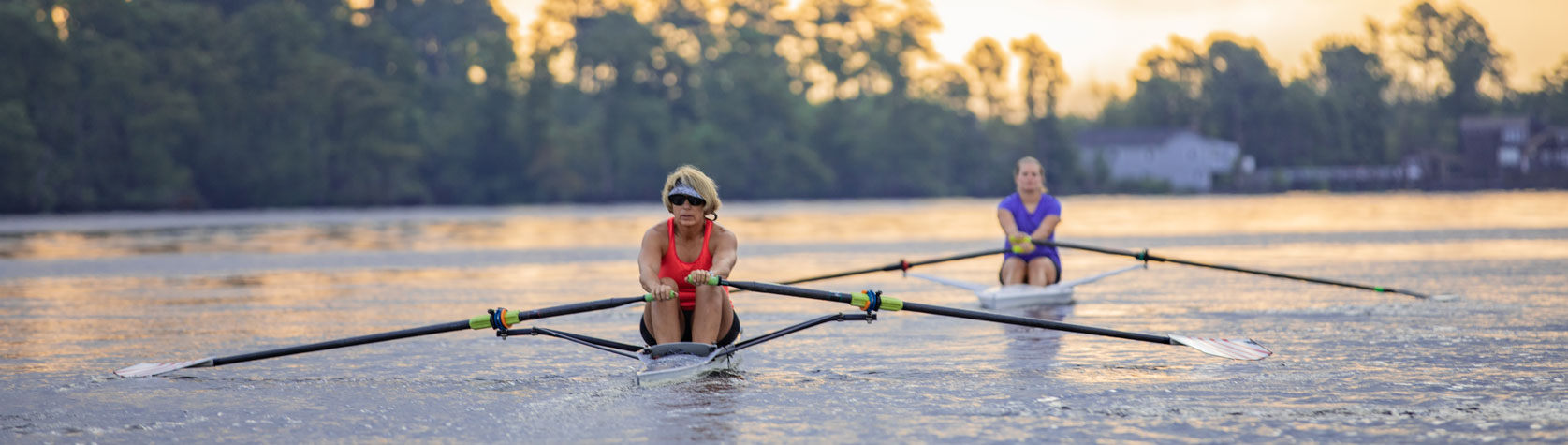 mother and daughter rowing on pasquotank river at sunset