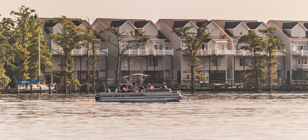 Pontoon boat in the river in front of apartments in Elizabeth City, North Carolina