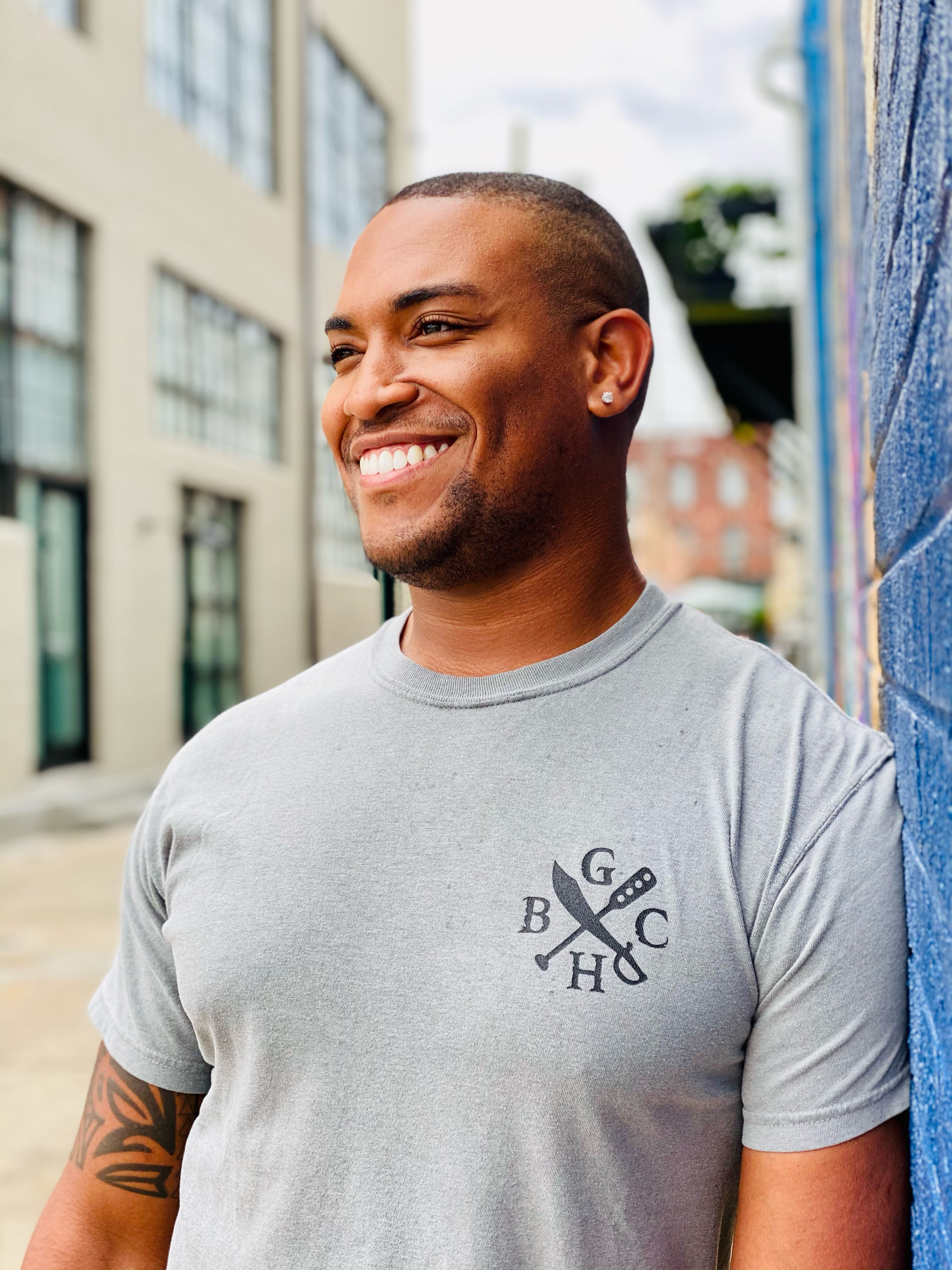 Man smiling in downtown Elizabeth City and wearing Ghost Harbor Brewery t-shirt