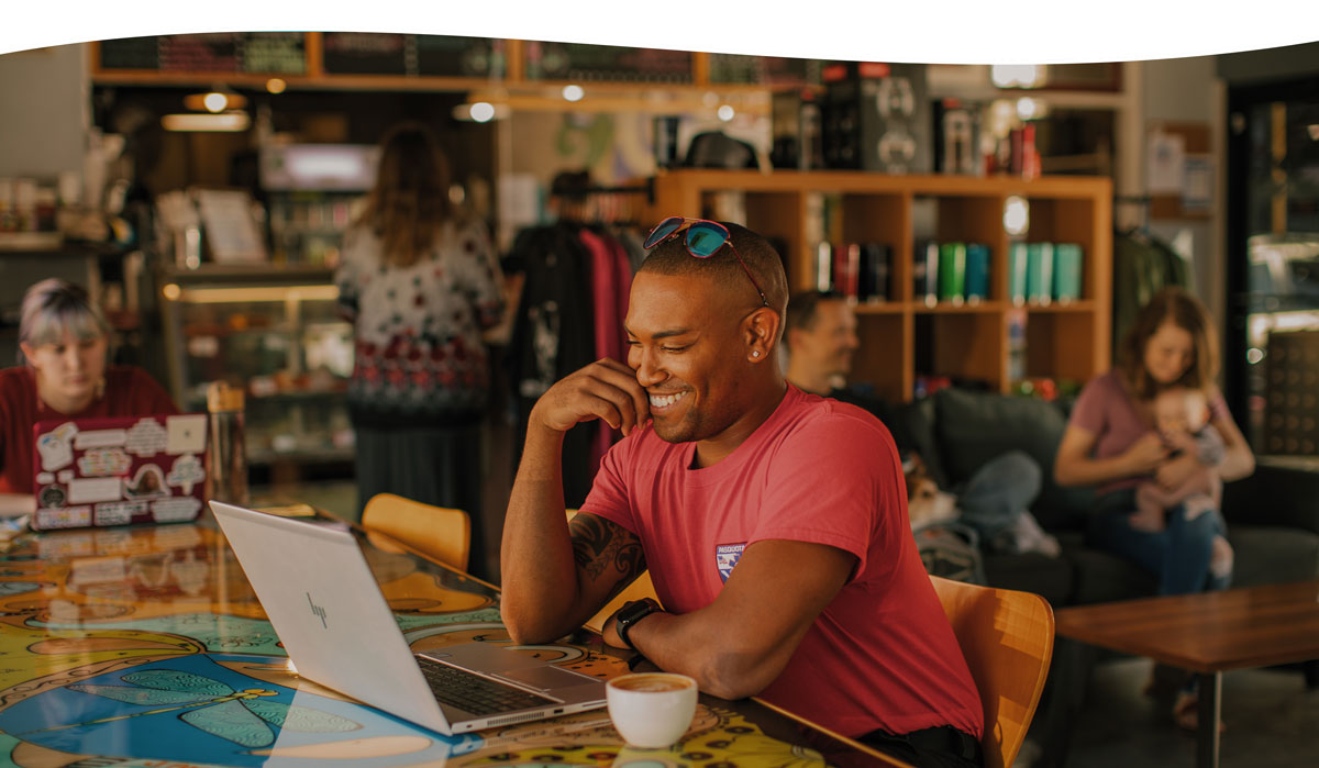 man sitting at coffeeshop smiling and using computer