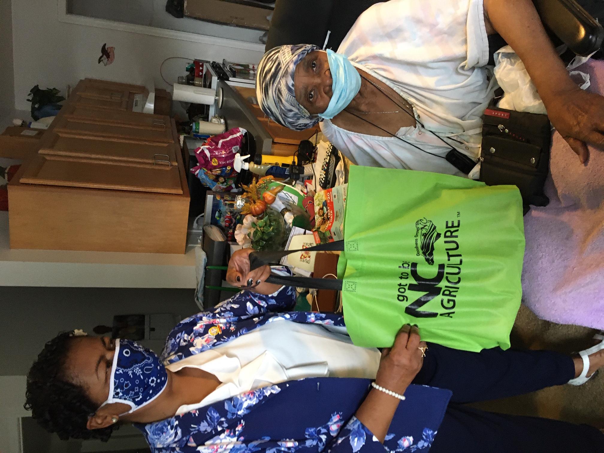 mayor wearing mask delivering food to elderly community member