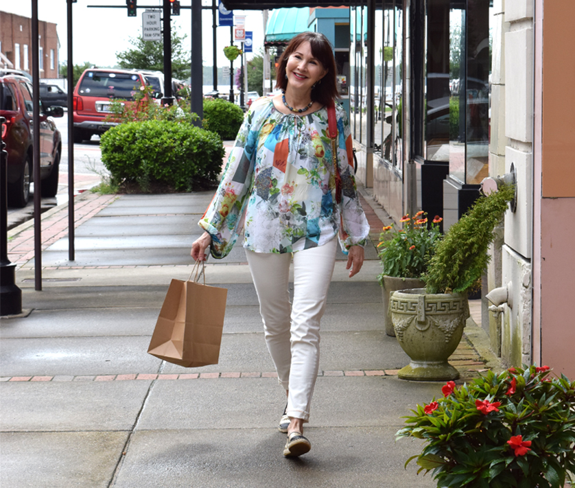 smiling woman walking on downtown street holding shopping bags