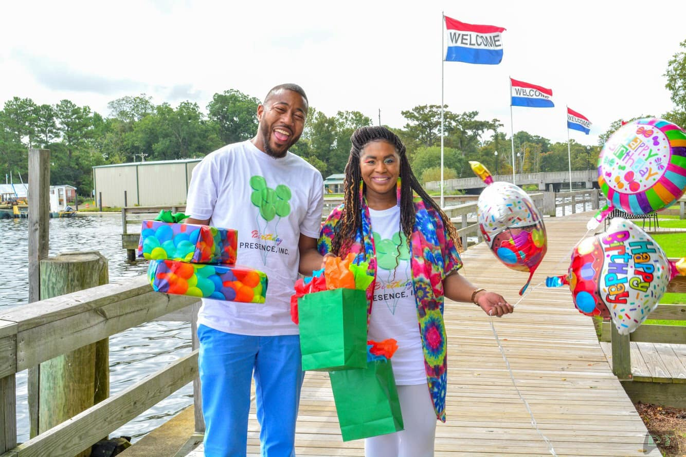 Michael and Tyreka Harrel holding balloons and donated birthday presents for children.