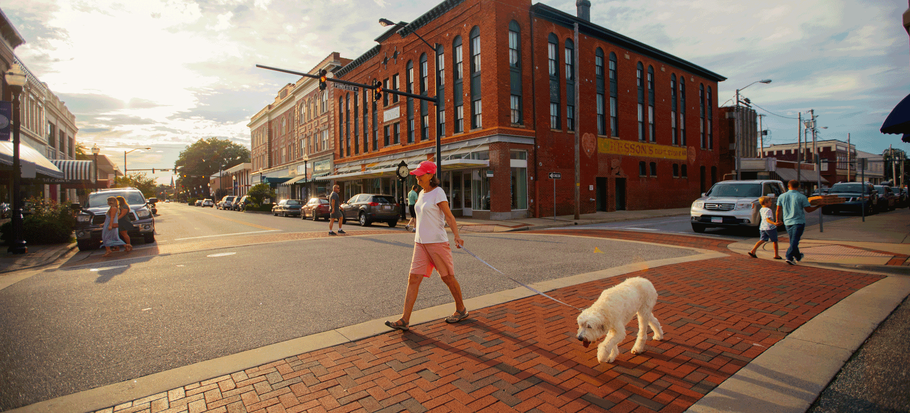 woman walking white poodle on downtown street in Elizabeth City, North Carolina