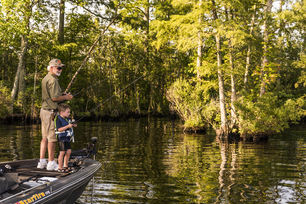grandfather and grandson fishing off bass boat in marsh