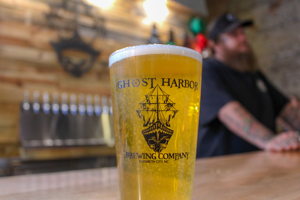 ghost harbor brewing company logoed pint glass on the bar of brewery with taps in background