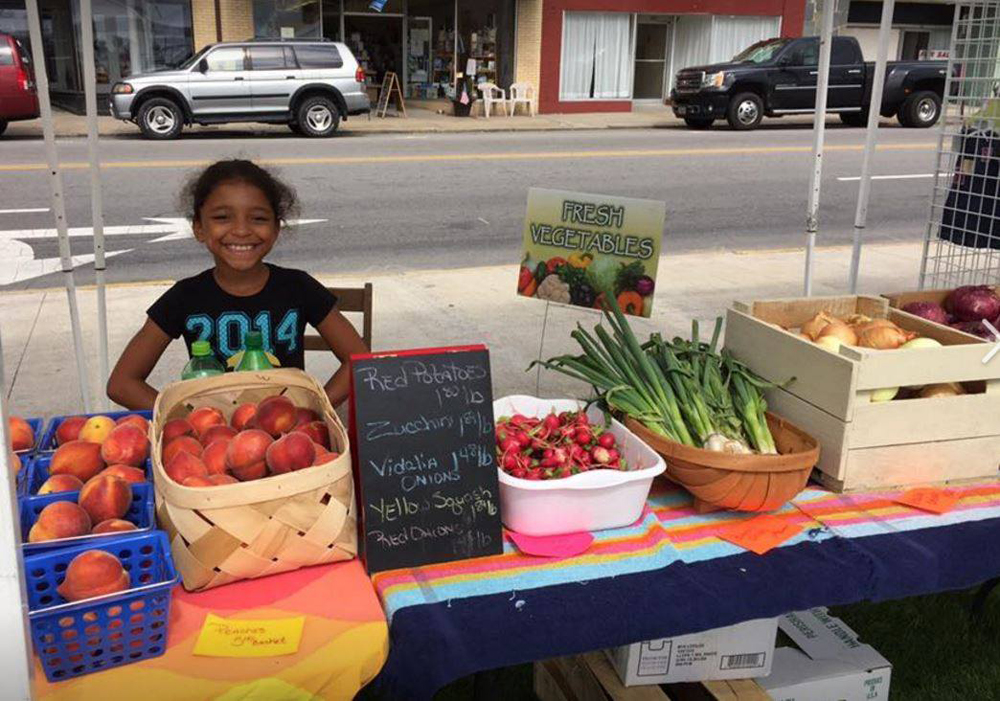 little girl at downtown waterfront market selling fruit and vegetables