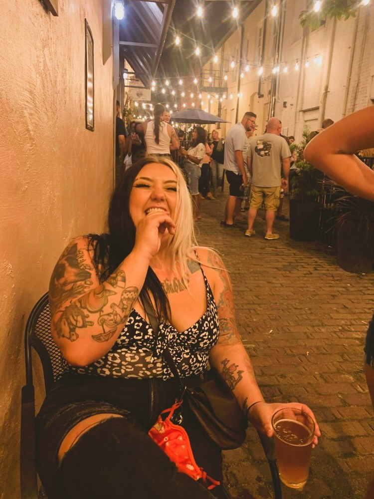 woman laughing with friends in Pailin's Alley in historic downtown Elizabeth City