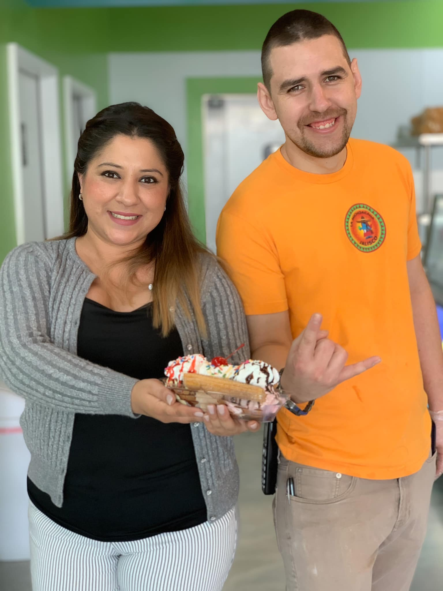 happy business owners holding churro sundae