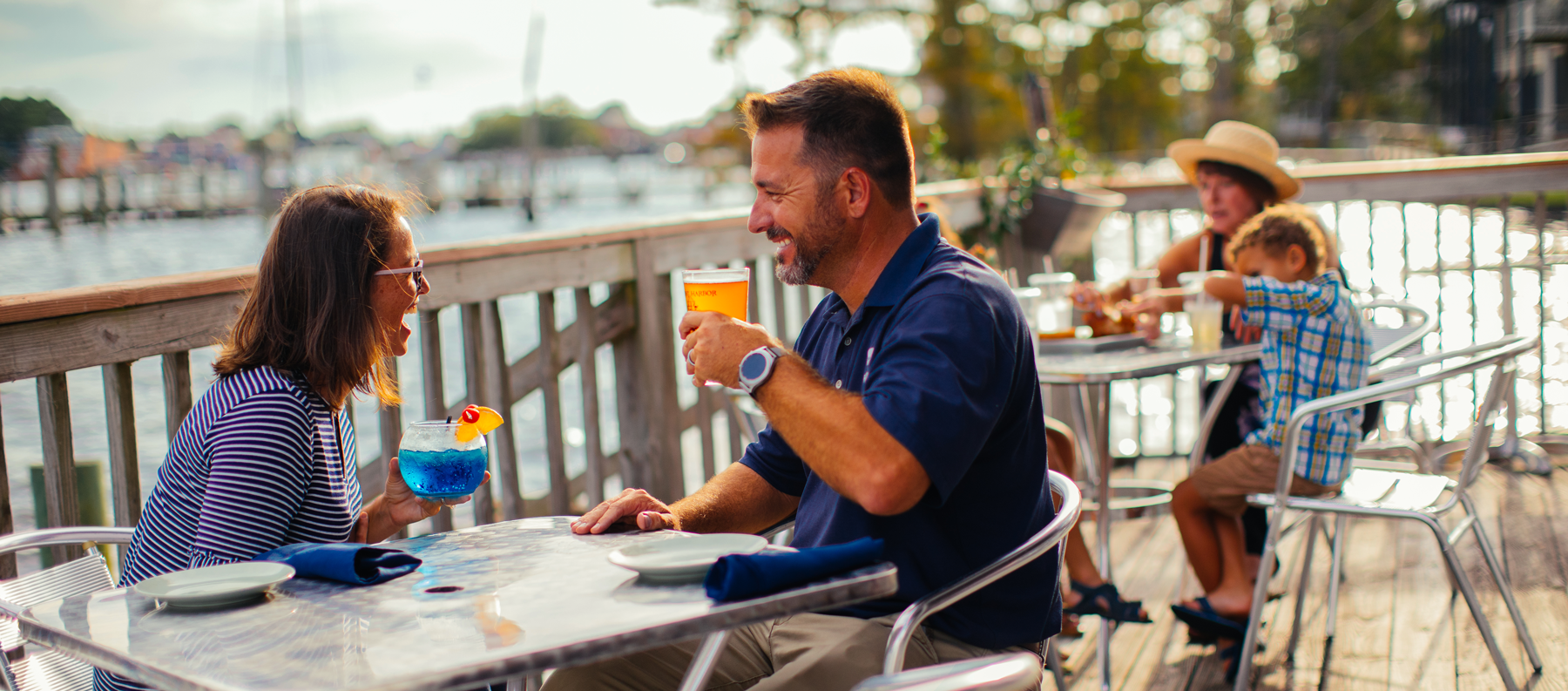 couple having a drink and dining outdoors with a waterfront view of the Pasquotank river