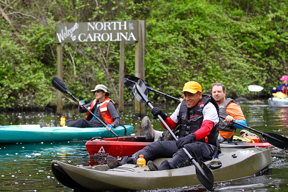 adults kayaking in winter clothes at dismal swamp state park north carolina