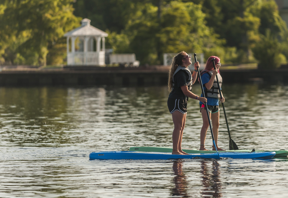 girls having fun stand up paddleboarding on the water