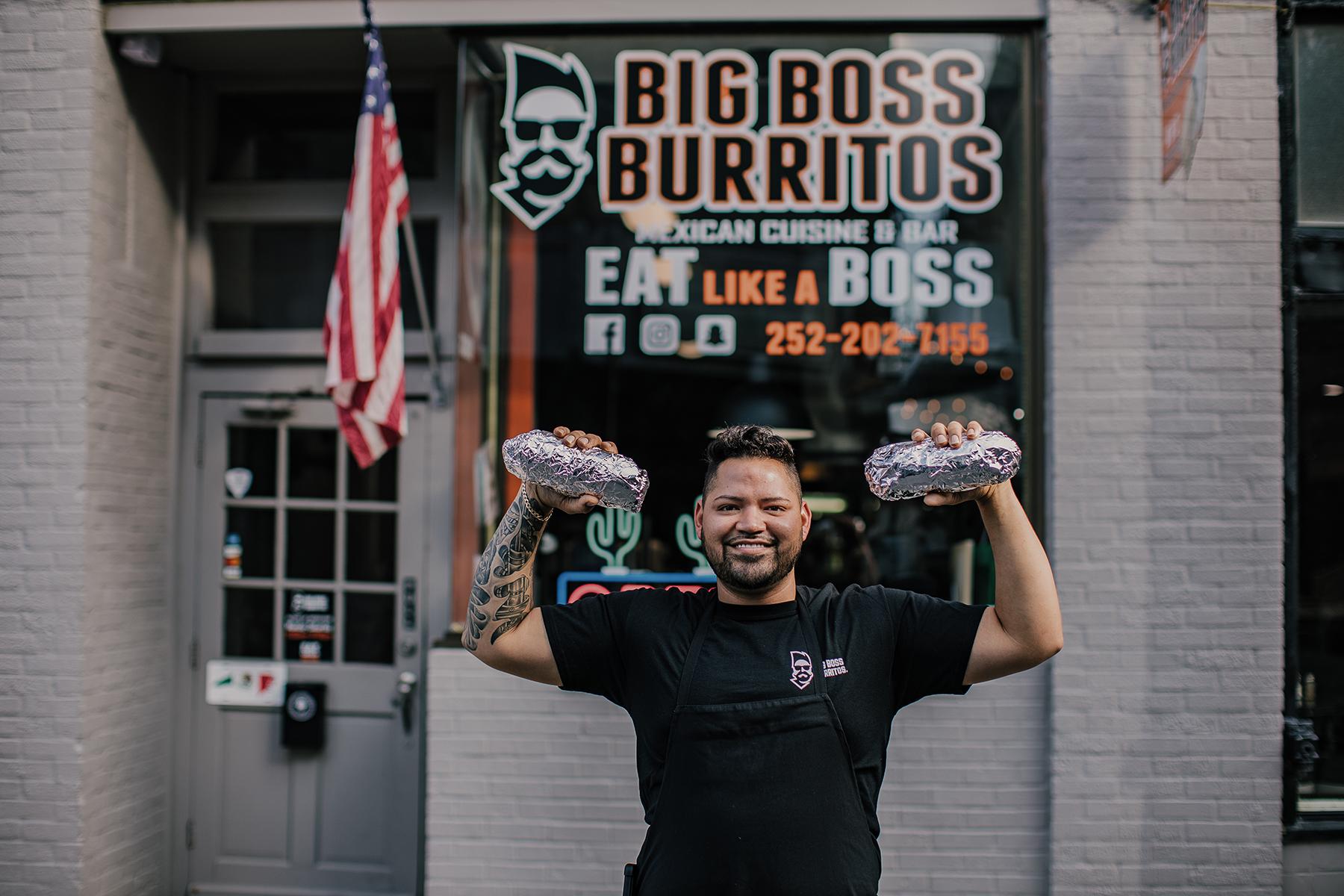 big boss burritos junior gonzales holding two giant burritos outside of restaurant