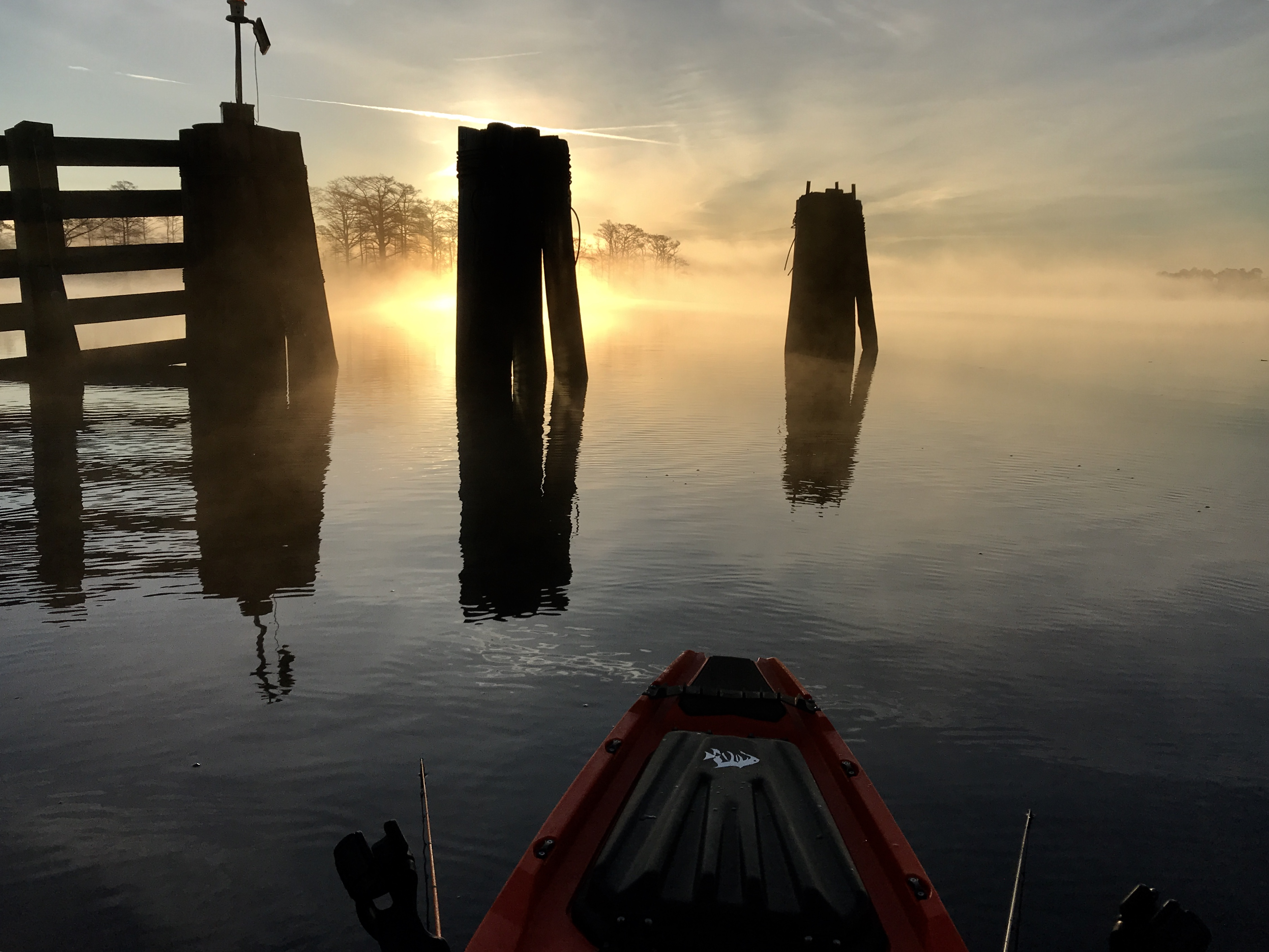 foggy waterscape with pilings at sunset