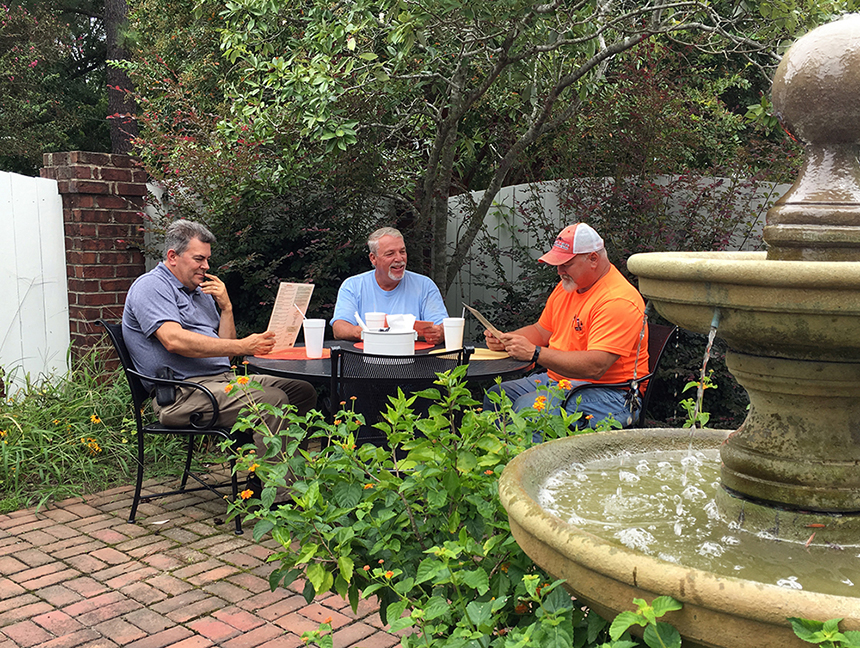 men sitting around outdoor dining table