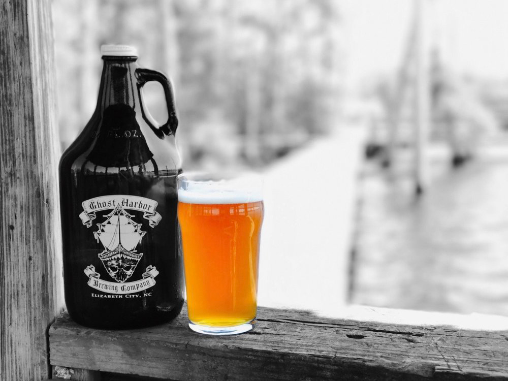 black and white ghost harbor brewery growler with pint of beer on the water