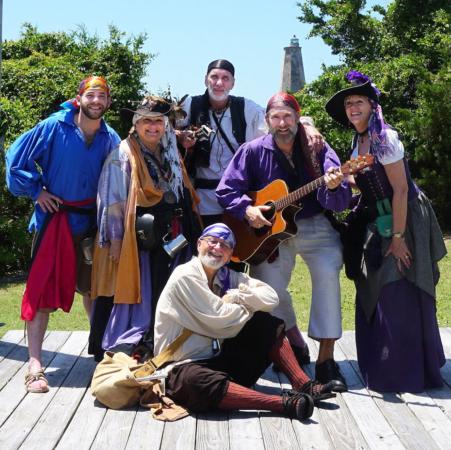 group of people wearing pirate attire and holding guitar