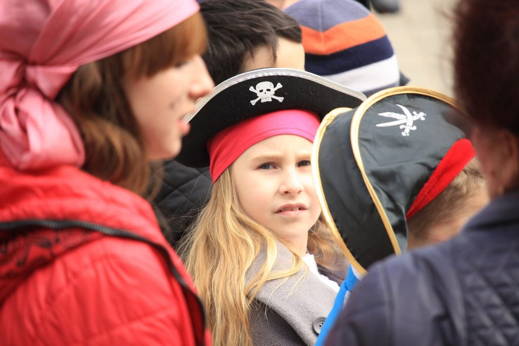 little girl looking at camera, group of kids wearing pirate hats