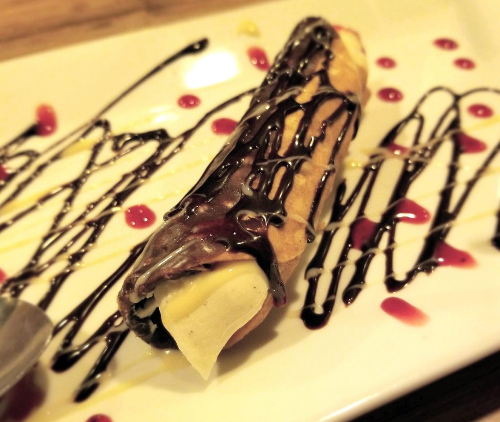 canoli drizzled in chocolate sauce