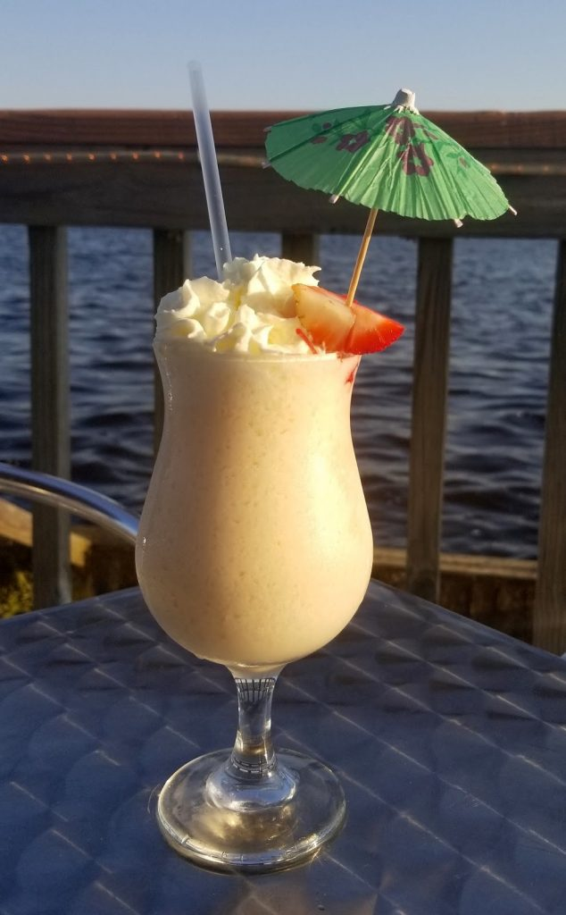 daiquiri with umbrella on patio overlooking the river